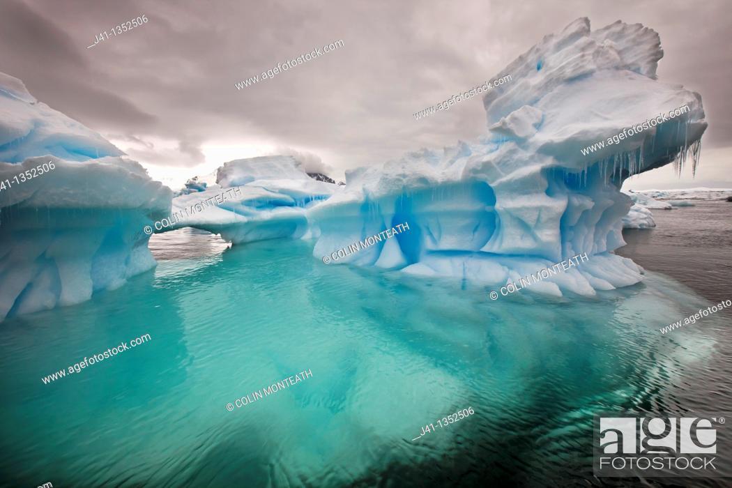 Stock Photo: Stormy sky over iceberg, Pleneau Island, Antarctic Peninsula.