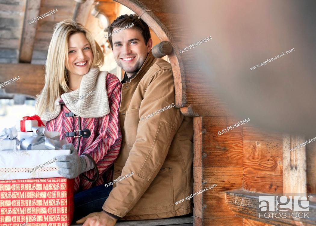 Stock Photo: Portrait of smiling couple with Christmas gifts on cabin porch.
