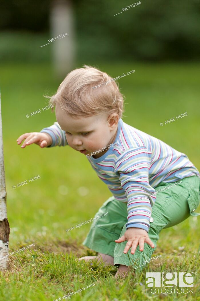 Stock Photo: child learning to walk loosing balance outdoors.