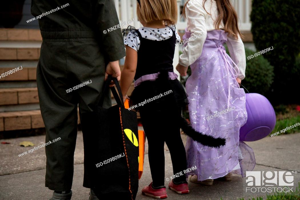 Imagen: Boy and sisters trick or treating waiting at porch stairway.