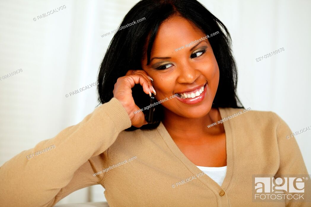 Stock Photo: Portrait of a stylish young woman looking down while is on mobile phone at home.