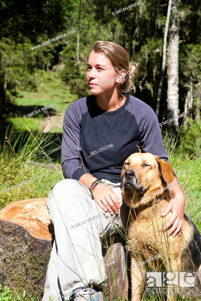 Stock Photo: A Girl Sits Relaxing Outside On A Warm Summers Day With Her Dog At Blue Duck Lodge, In Whanganui National Park; Whakahoro, New Zealand.