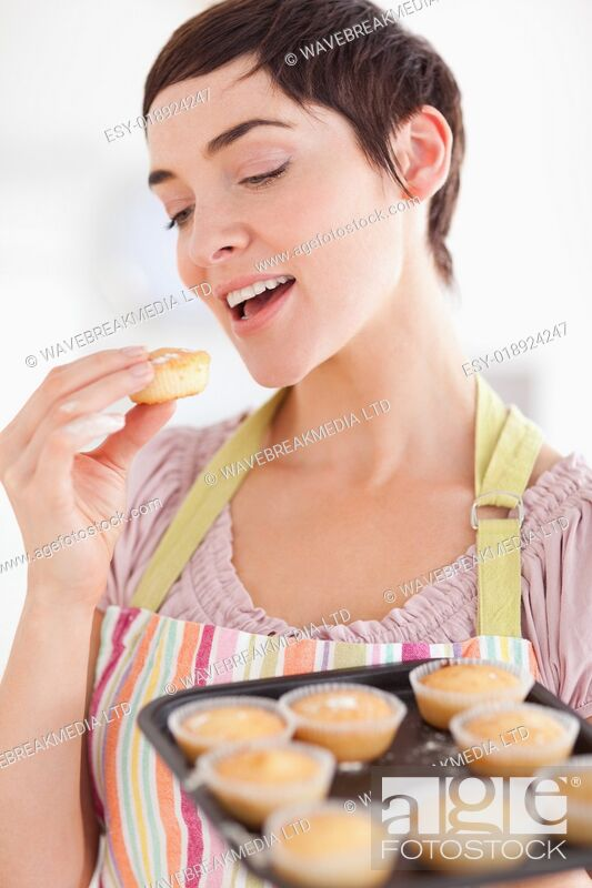 Stock Photo: Smiling brunette woman showing muffins while eating one.