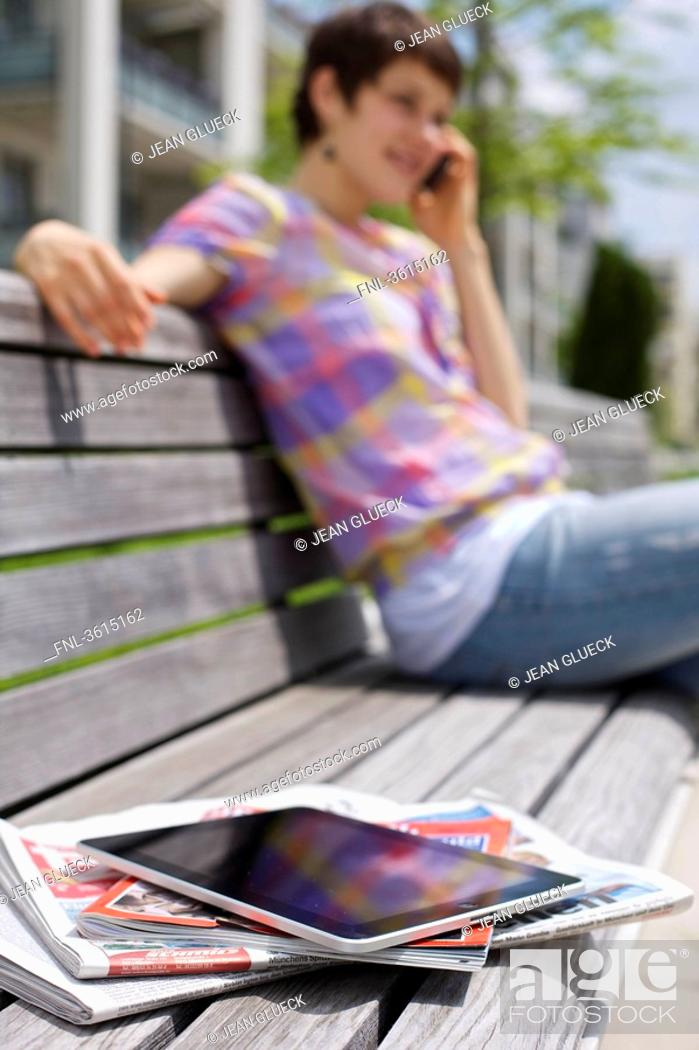 Stock Photo: Young woman with cell phone, iPad, newspapers and magazine on a bench.