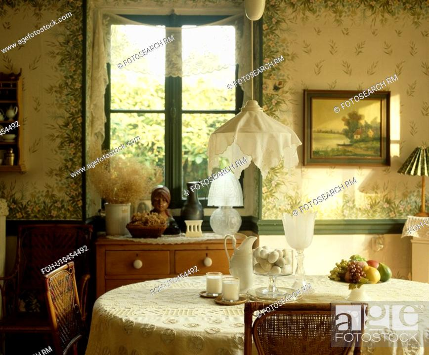Stock Photo   Cotton Lampshade On Pendant Lamp Above Table With Lace Cloth  In Edwardian Style Living Room With Painted Floral Walls