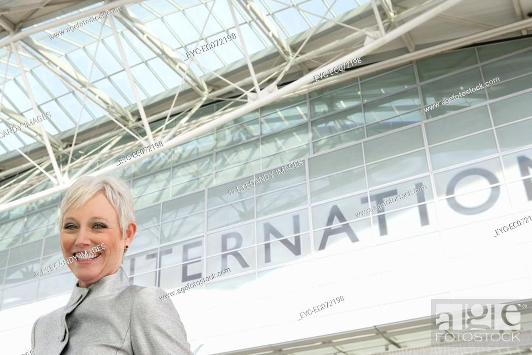 Stock Photo: Mature woman standing in front of airport.