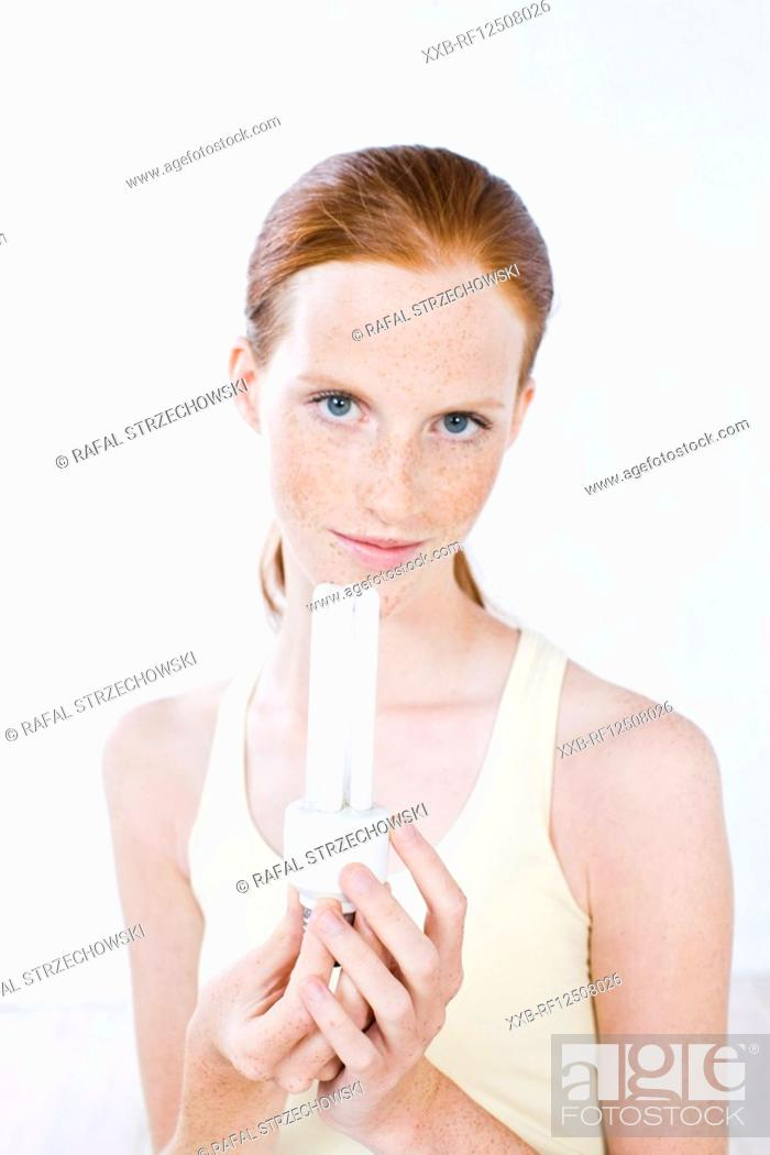 Stock Photo: young woman holding saving-energy light bulb.