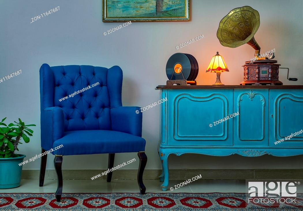 Photo de stock: Interior shot of blue armchair, vintage wooden light blue sideboard, lighted antique table lamp, old phonograph (gramophone).