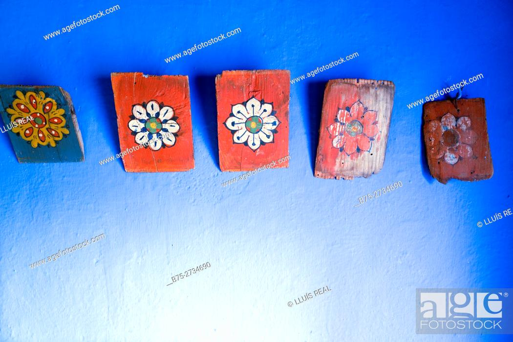 Stock Photo: Paintings on wood hung on a blue wall. Chaouen, Morocco.