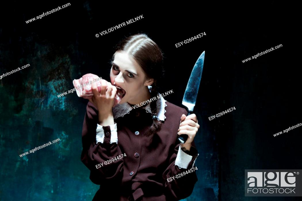 Stock Photo: Portrait of a young girl with knife and and a piece of raw meat on a plate. Girl in school uniform as killer. The image in the style of Halloween.
