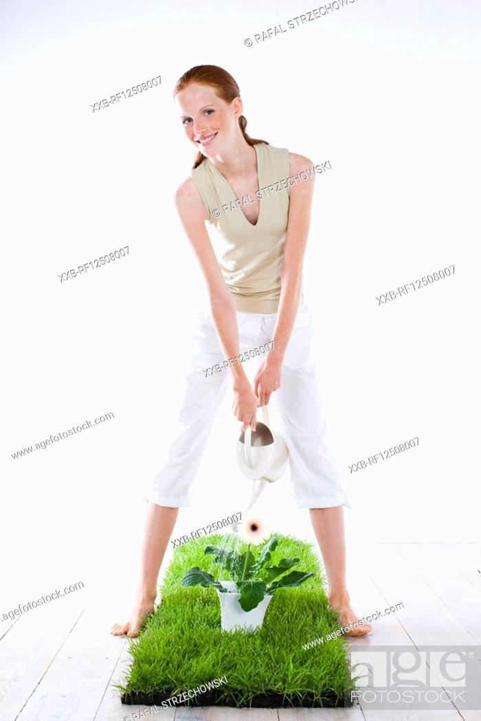 Stock Photo: young woman watering plant.