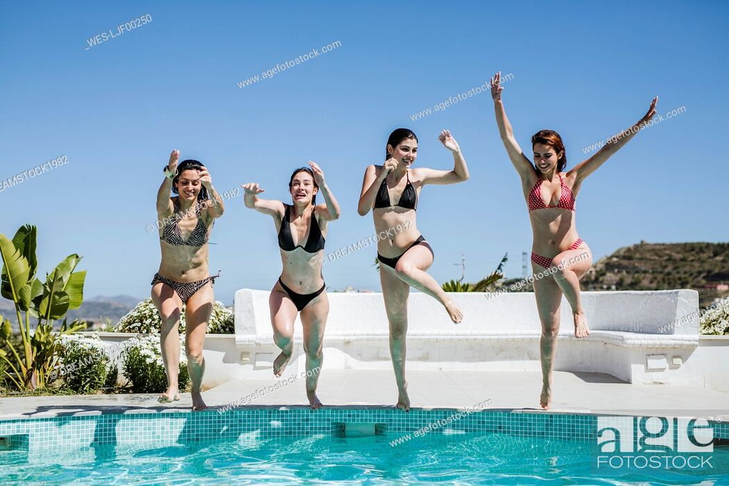 Stock Photo: Young women enjoying the summer time at pool, jumping into the water.