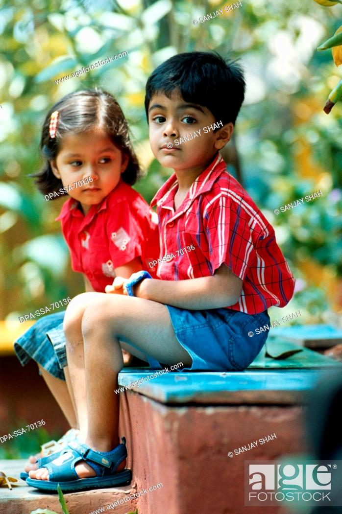 Young Indian boy Yash and girl Esha sitting on steps looking