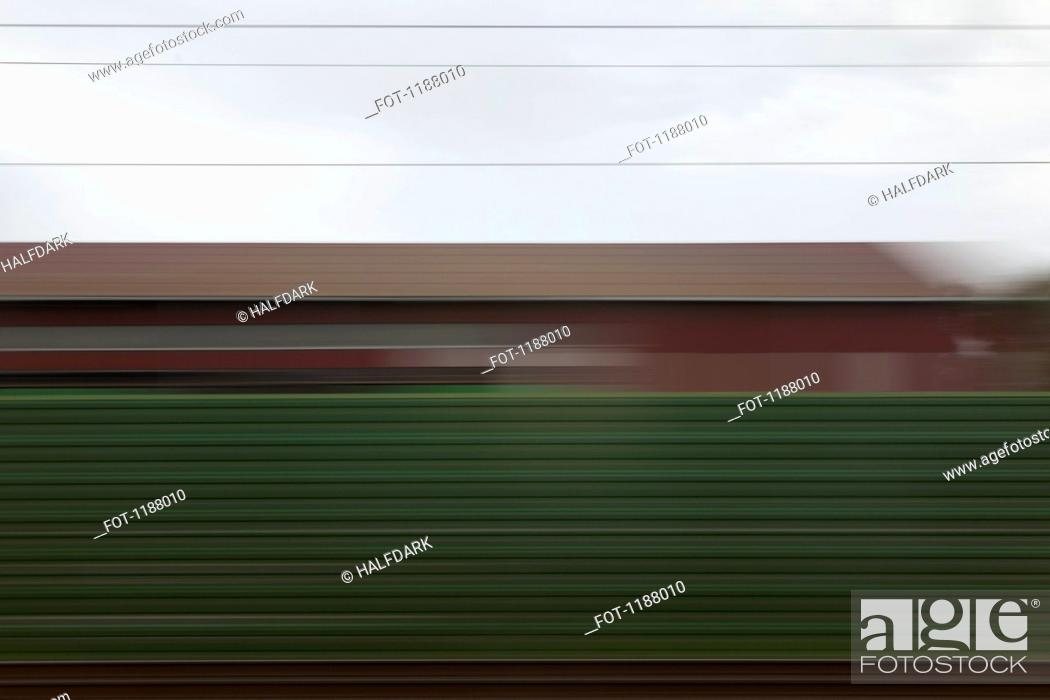 Stock Photo: A building and abstract pattern in blurred motion viewed from moving train.