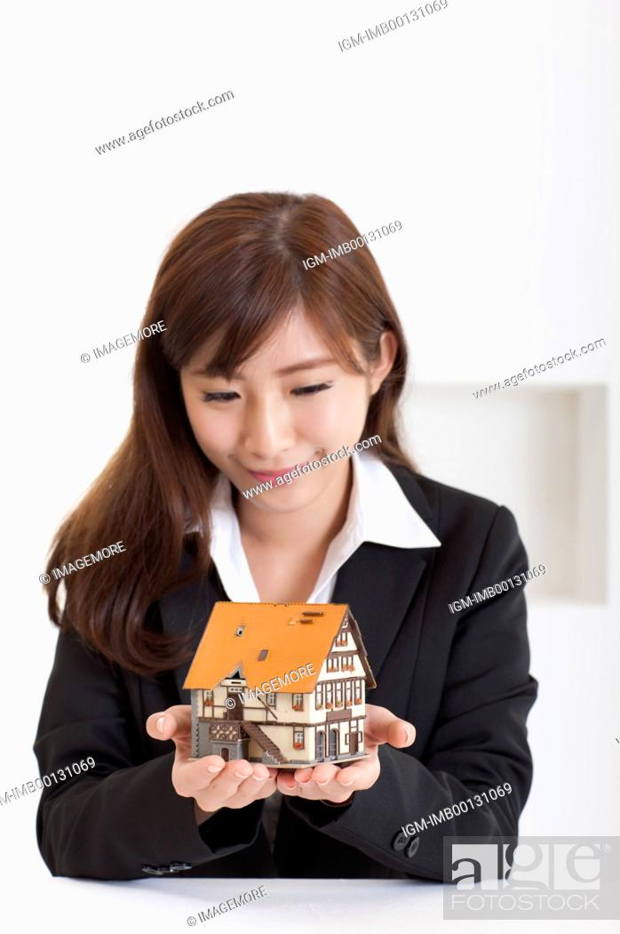 Imagen: Young business woman holding house model and looking down with smile,.