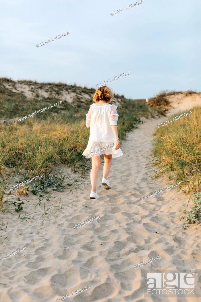 Stock Photo: Young woman in white dress walking on coastal dunes, rear view, Menemsha, Martha's Vineyard, Massachusetts, USA.