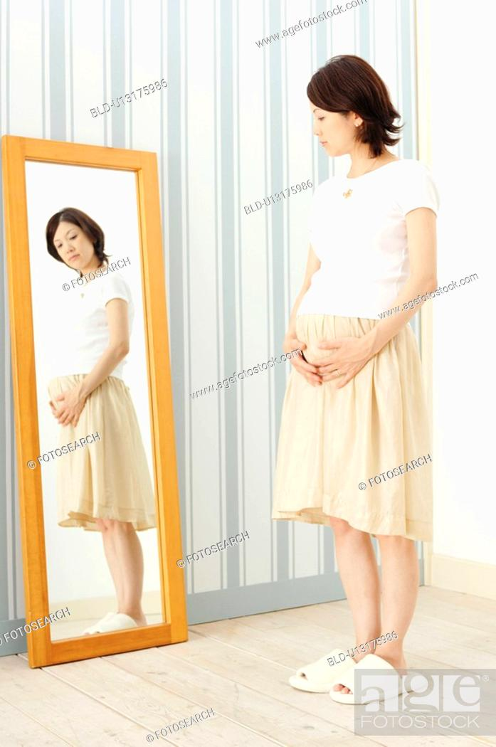 Stock Photo: Pregnant woman watching a mirror.