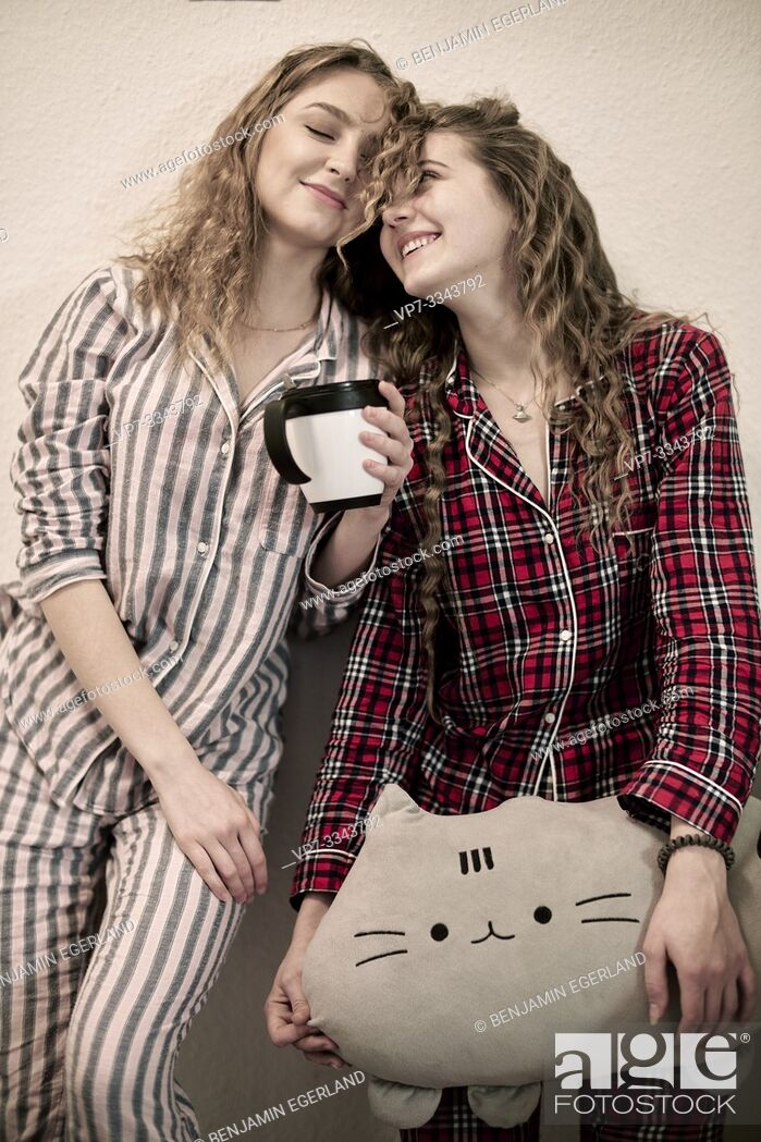 Stock Photo: two tired friends in pyjamas with plushie and cup.