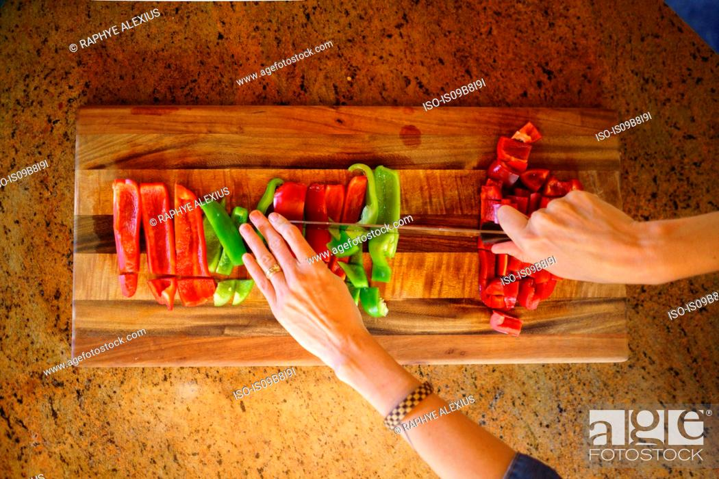 Stock Photo: Overhead view of woman's hands chopping red and green peppers.