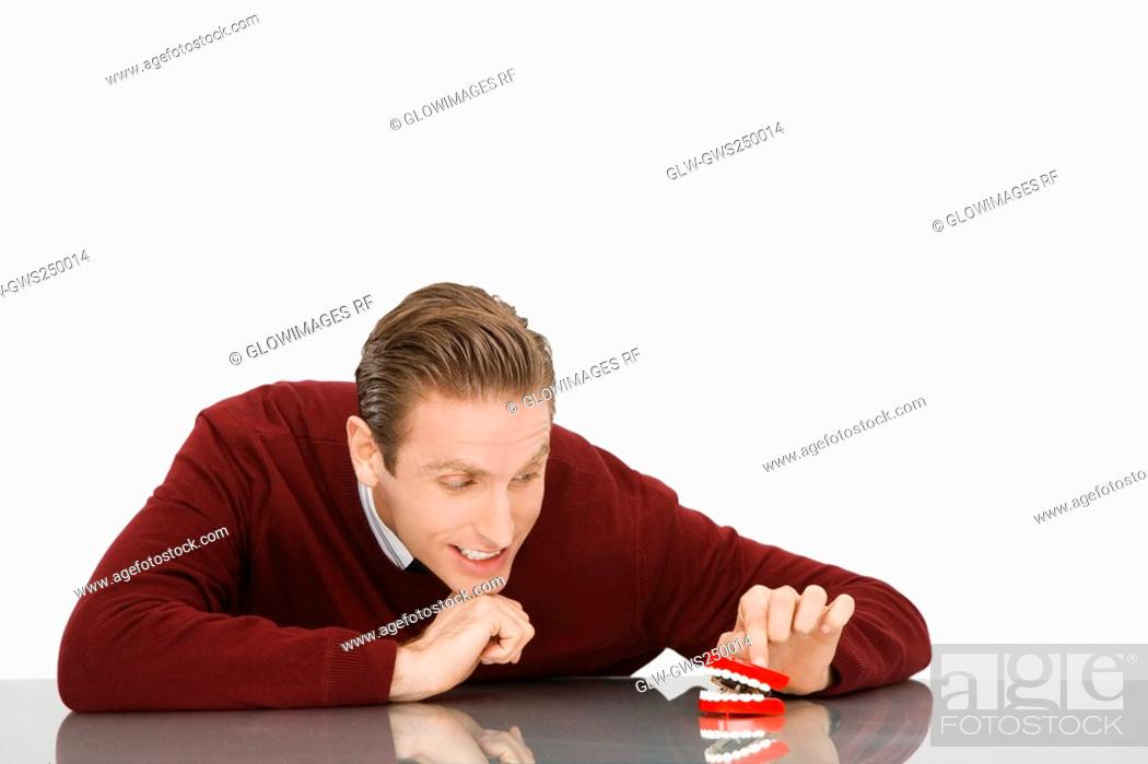 Stock Photo: Businessman looking at dentures and smiling.