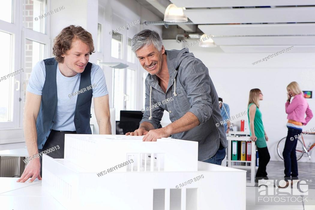 Stock Photo: Germany, Bavaria, Munich, Men watching architectural model in office, colleagues talking in background.