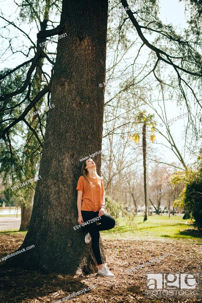 Imagen: Young blonde woman supported on a tree with black jeans.