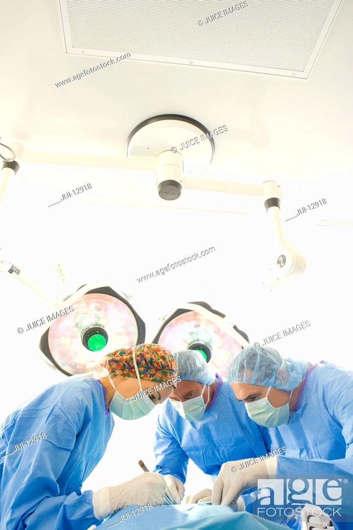 Stock Photo: Surgeons operating on patient.