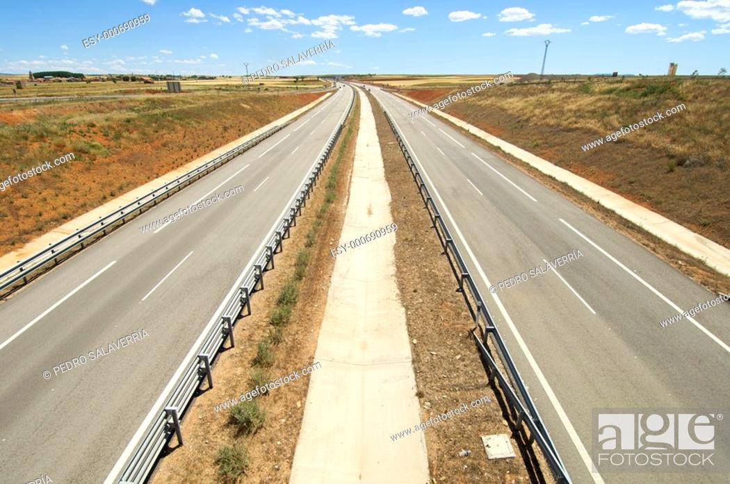 Stock Photo: highway with blue and cloudy sky.