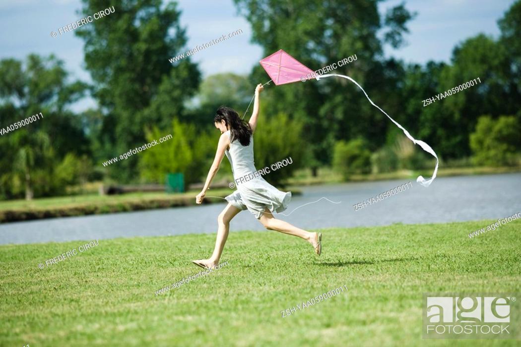 Stock Photo: Teen girl running with kite, full length.