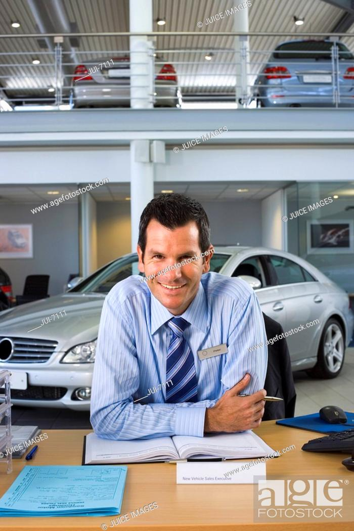 Stock Photo: Car salesman sitting at desk in car showroom, smiling, front view, portrait.
