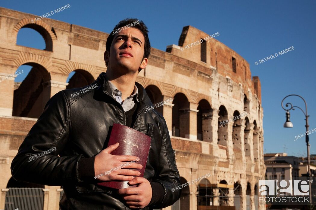 Imagen: A young man stands holding a Bible and looks up with the Colosseum in the background; Rome, Italy.