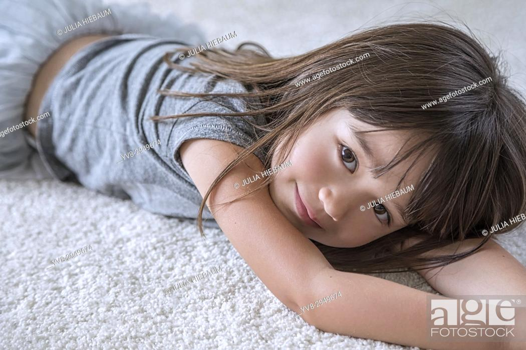Stock Photo: Five year old girl laying on the carpet in her room.