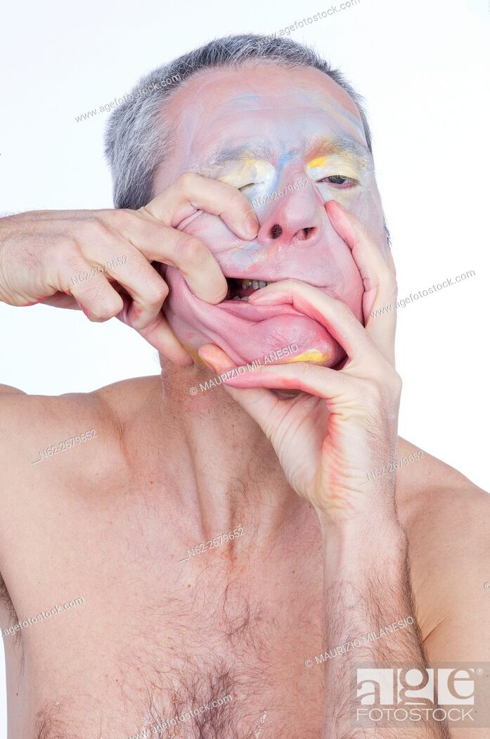 Stock Photo: Portrait of a crazy clown, he smeared makeup on the face with his hands vigorously.