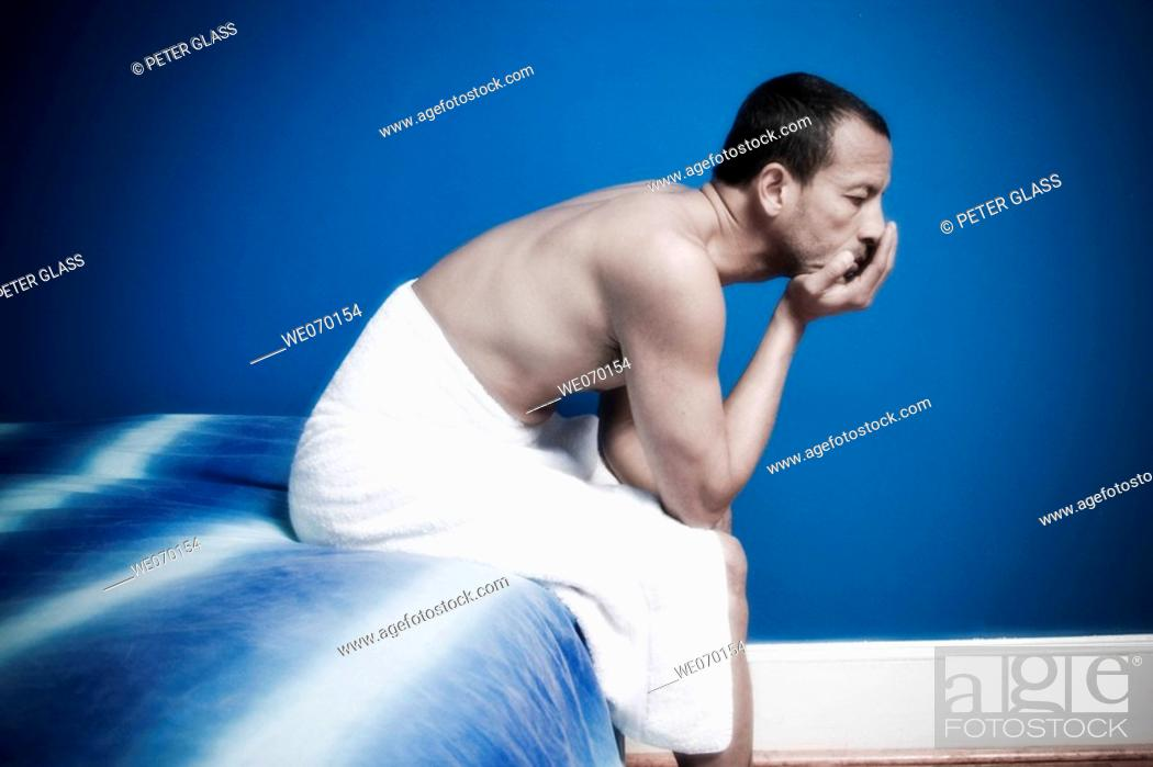 Stock Photo: Hispanic man, wearing only a towel, sitting on his bed.