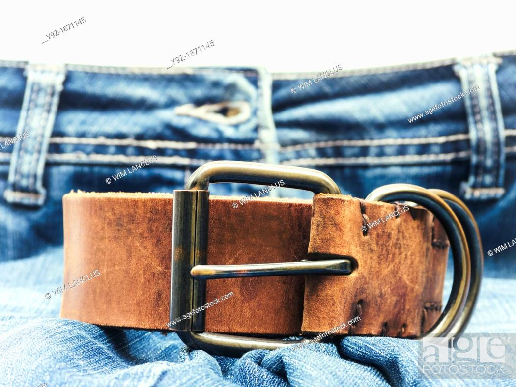 Stock Photo: Jeans with brown leather belt in foreground.