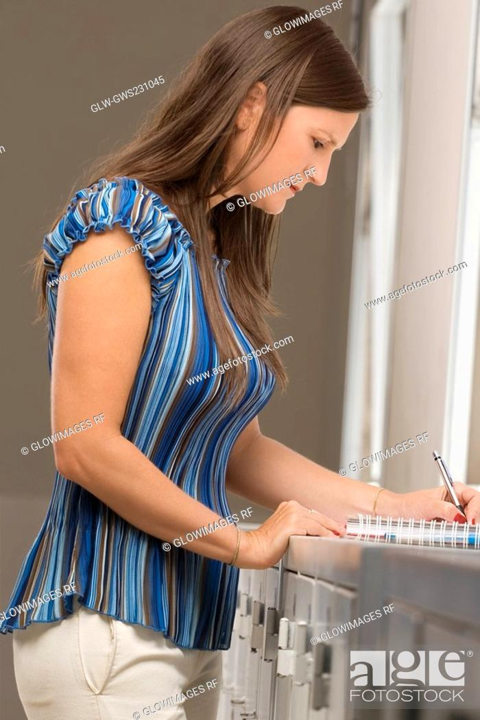 Stock Photo: Side profile of a mid adult woman writing in a spiral notebook.