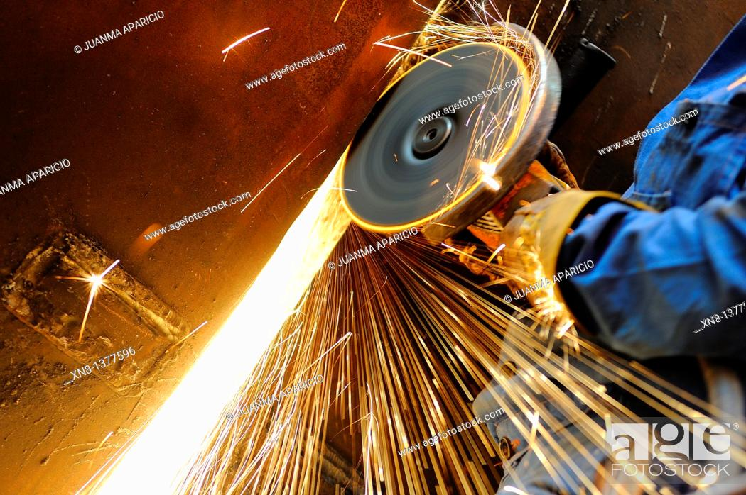 Stock Photo: Close-up of heavy industry worker with grinding machine throwing a splash of sparks.