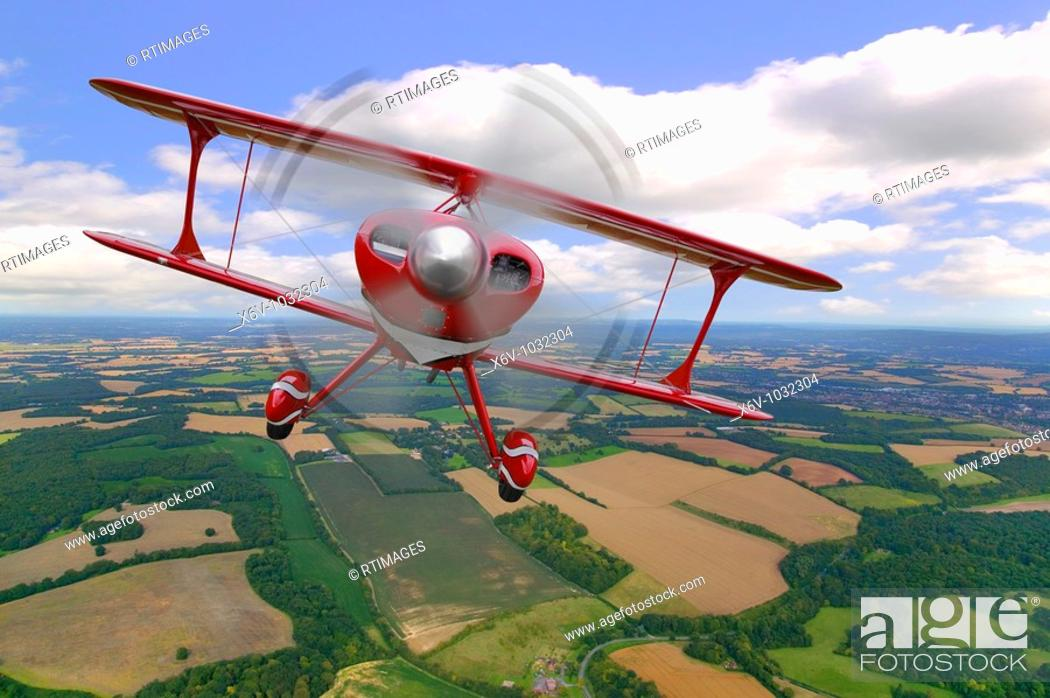Stock Photo: A red stunt biplane in flight over rural countryside.
