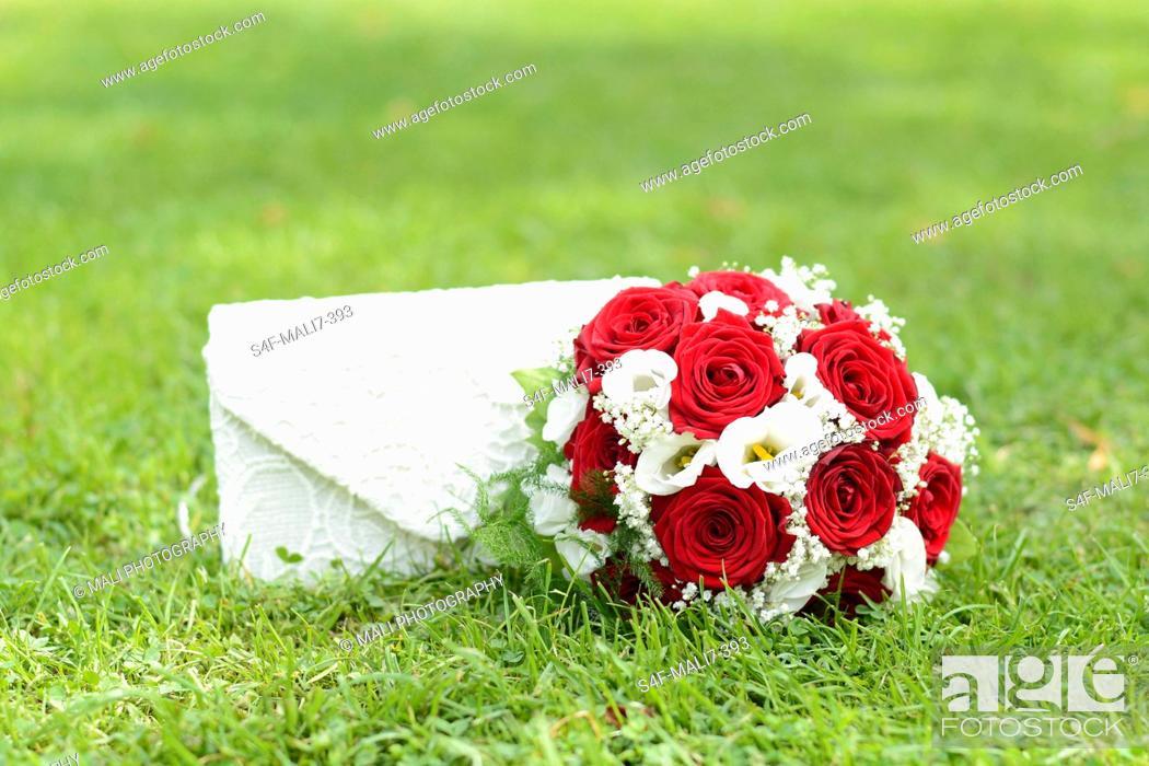 Imagen: Brautstrauß und Handtasche auf dem Rasen.