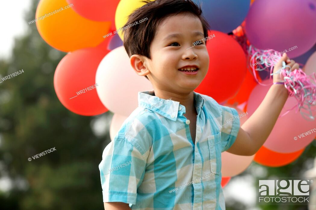 Imagen: Boy holding bunch of balloons.