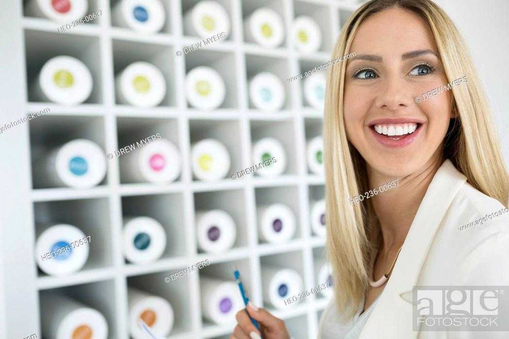 Smiling architect shelves of color coded blueprint tubes stock stock photo smiling architect shelves of color coded blueprint tubes malvernweather Images