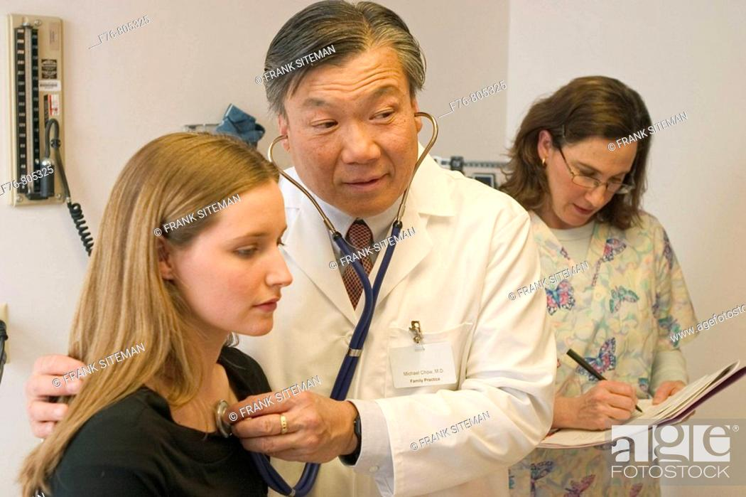 Stock Photo: Asian doctor, listening to chest sounds of female patient, with stethoscope, in exam room of medical office with nurse, taking notes.