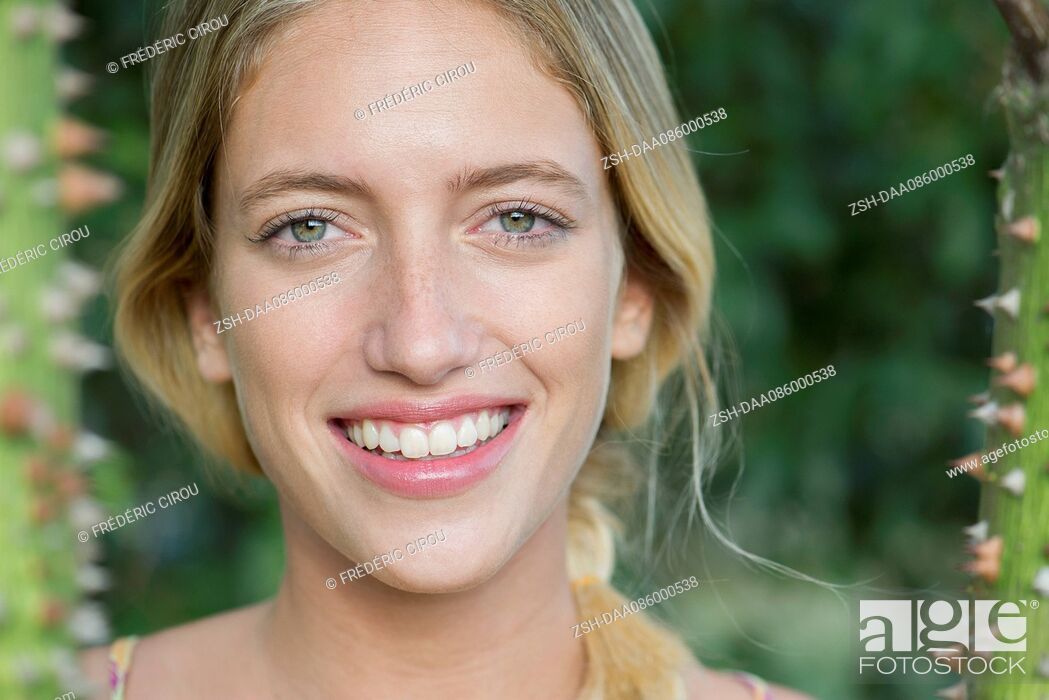 Stock Photo: Young woman smiling cheerfully, portrait.