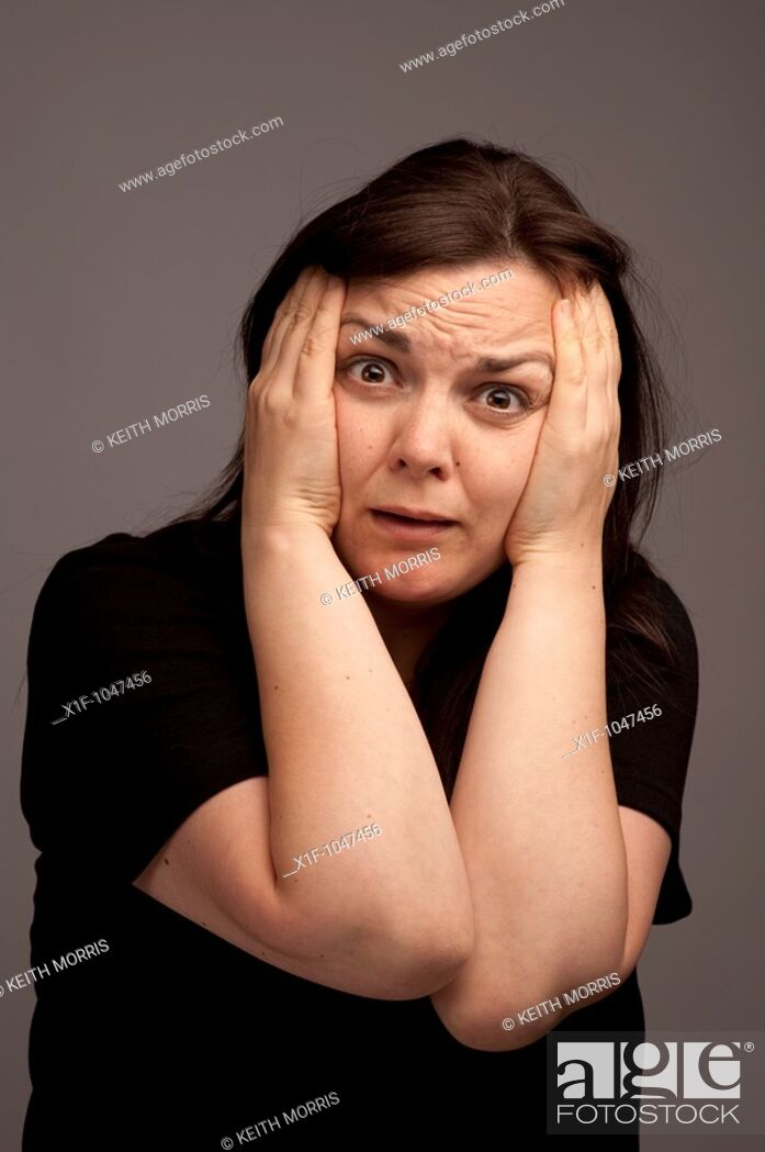 Stock Photo: a worried panicked anxious concerned frightened horrifed terrified woman with her head in her hands.