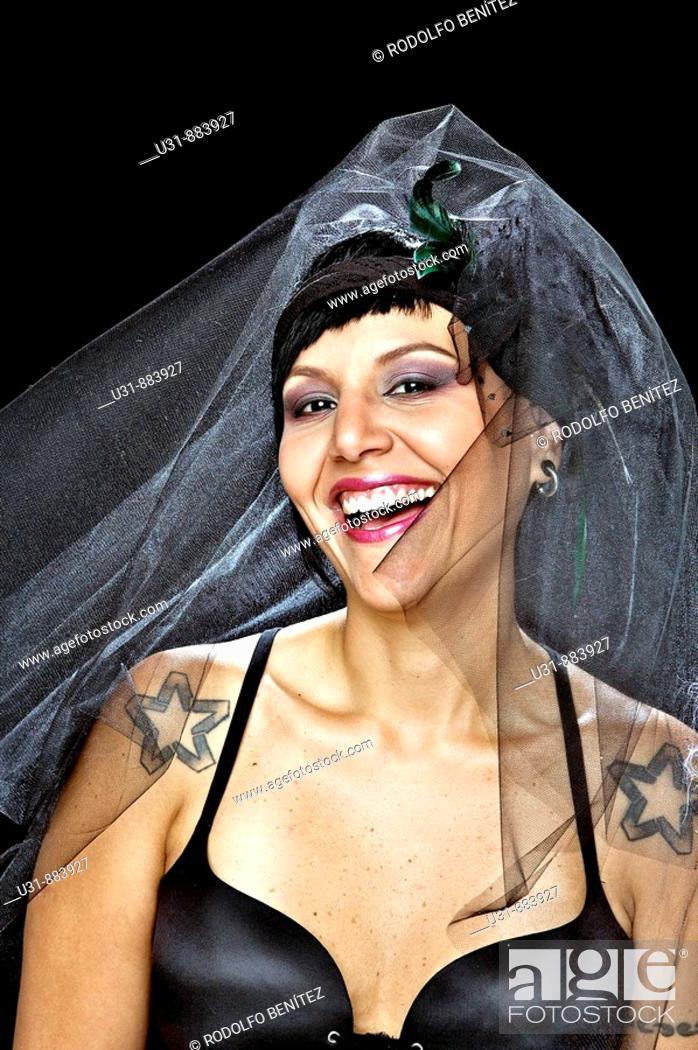Stock Photo: Punk Bride in her late 20s in a studio setting wearing a black wedding dress smiles.