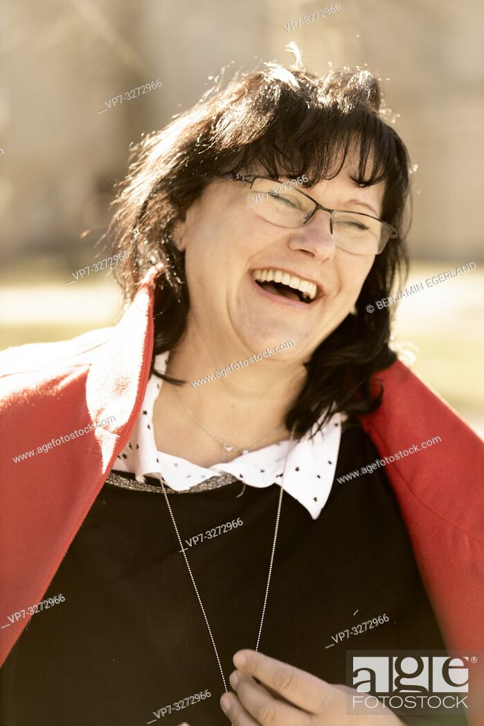 Stock Photo: happy mature woman laughing outdoors in sunlight, in Cottbus, Brandenburg, Germany.