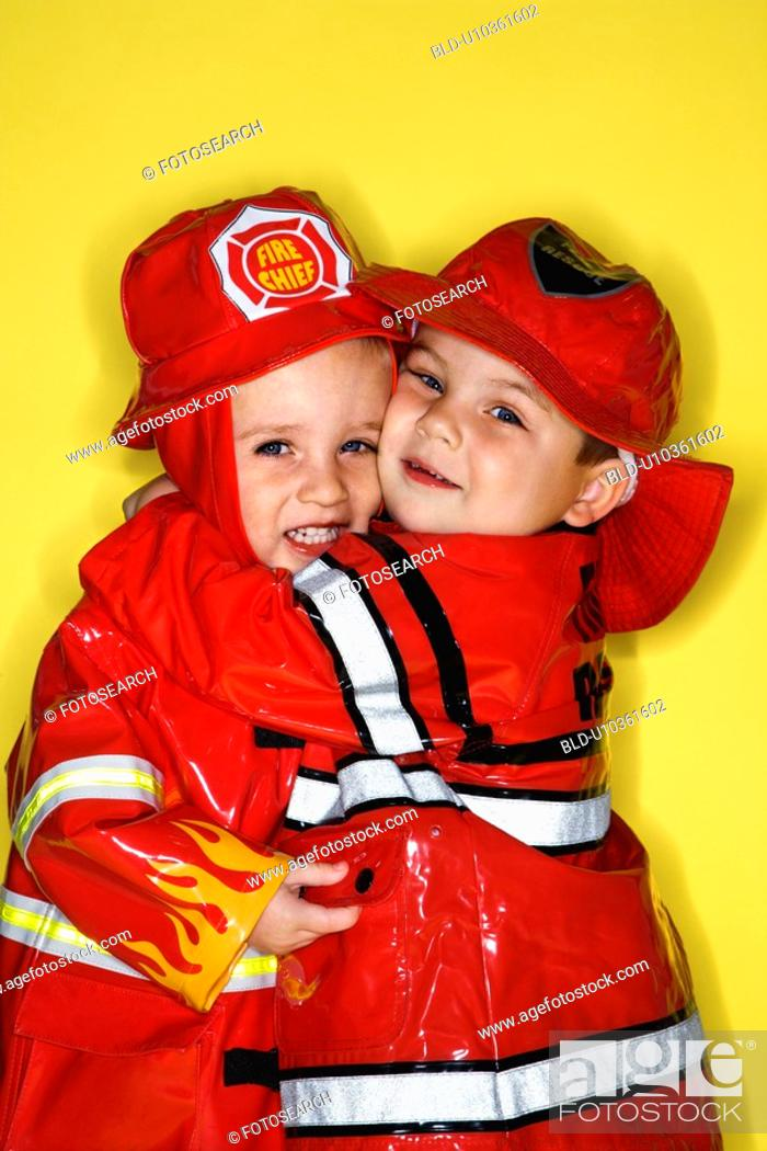 Stock Photo: Twin boys dressed as firemen hugging against yellow background.