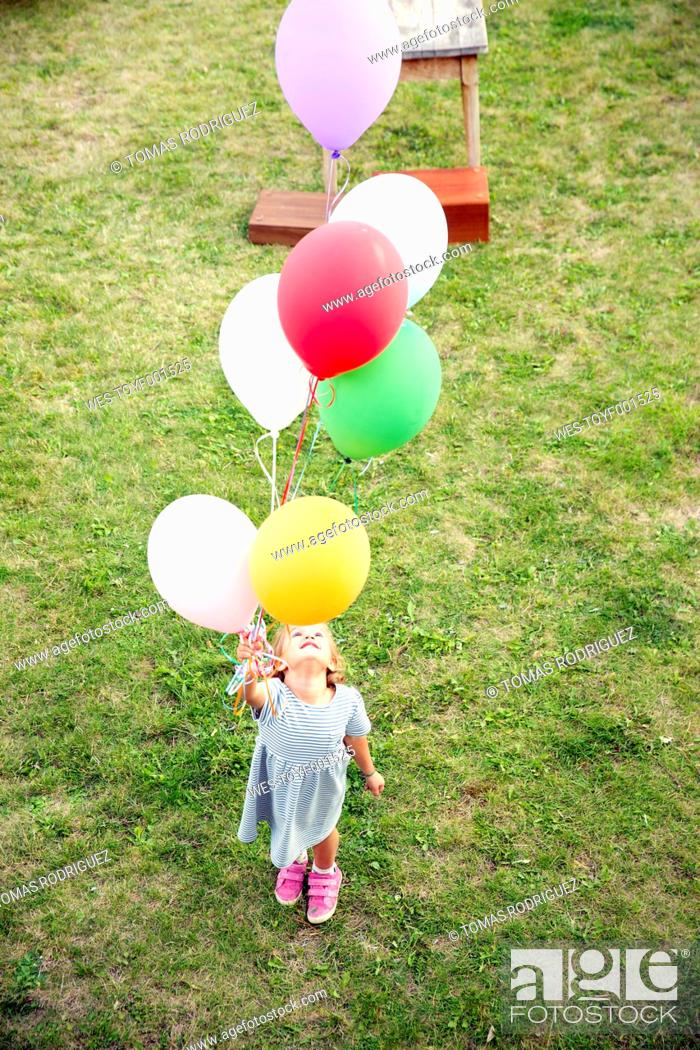 Stock Photo: Girl standing in garden holding colorful balloons.