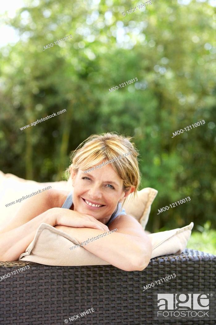 Stock Photo: Middle-aged woman sitting on sofa in garden portrait.