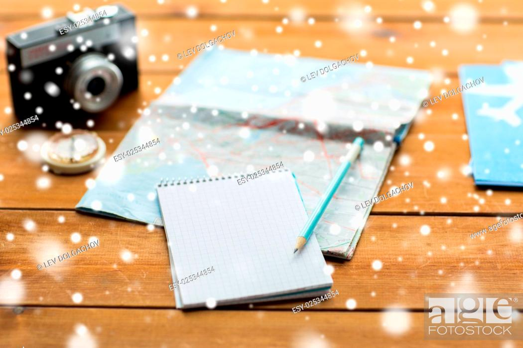 Stock Photo: vacation, tourism, travel, winter holidays and objects concept - close up of blank notepad with map and airplane tickets.